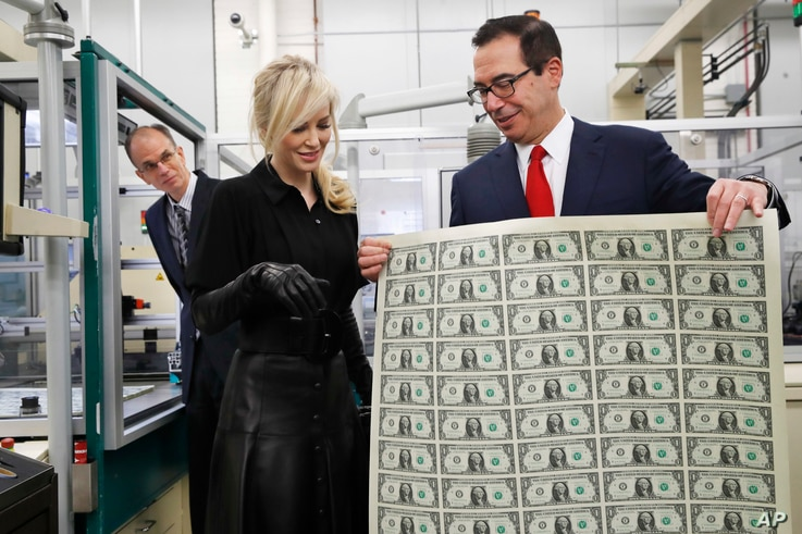 Treasury Secretary Steven Mnuchin, right, shows his wife Louise Linton a sheet of new $1 bills, the first currency notes bearing his and U.S. Treasurer Jovita Carranza's signatures, Wednesday, Nov. 15, 2017, at the Bureau of Engraving and Printing (B...