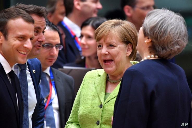 British Prime Minister Theresa May, right, speaks with from left, French President Emmanuel Macron, Luxembourg's Prime Minister Xavier Bettel and German Chancellor Angela Merkel before a round table meeting at an EU summit in Brussels, June 22, 2017....