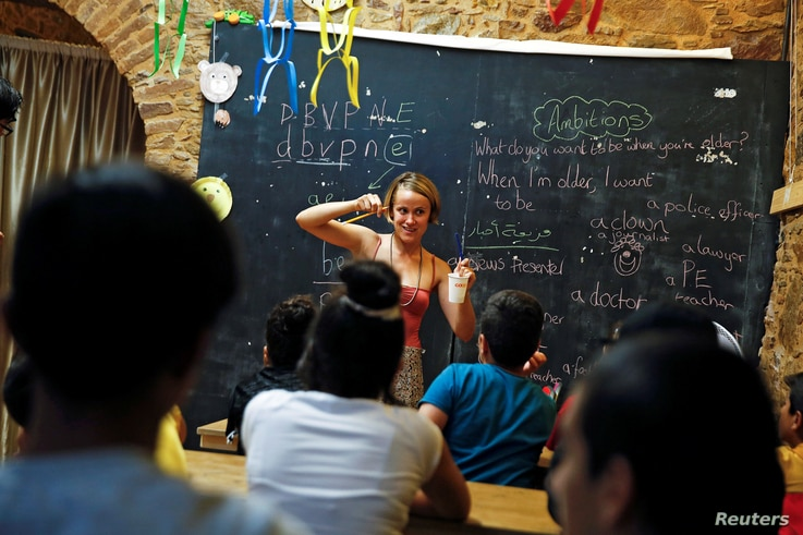 "British volunteer primary school teacher Helen Brannigan holds a pen and a cup as she conducts an English class for refugee children at the volunteer-run ""Refugee Education Chios"" school on the island of Chios, Greece, Sept. 6, 2016."