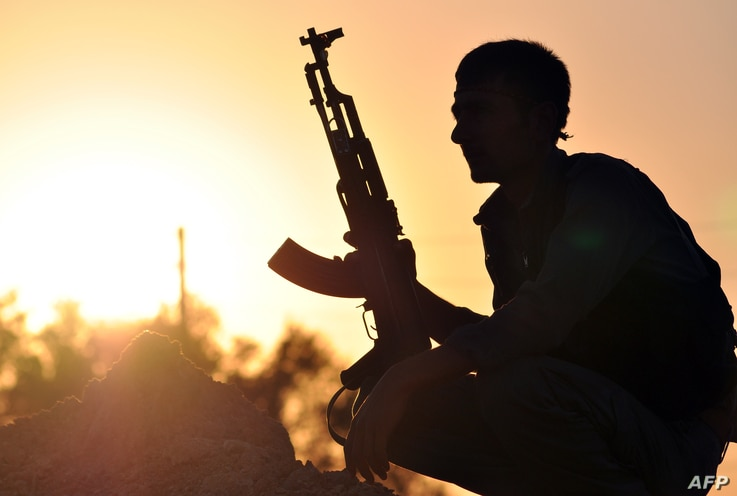 FILE - A fighter from the Kurdish People Protection Unit (YPG) poses for a photo at sunset in the Syrian town of Ain Issi, some 50 kilometres north of Raqqa, uring clashes between IS group jihadists and YPG fighters on July 10, 2015.