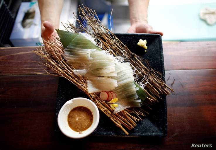 A chef serves flying squid sashimi at a seafood restaurant in Tokyo, Japan, Sept. 27, 2018.