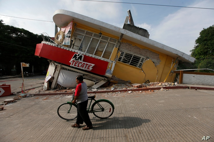 A man walks his bike past a building felled by a 7.1 earthquake, in Jojutla, Morelos state, Mexico, Sept. 20, 2017.
