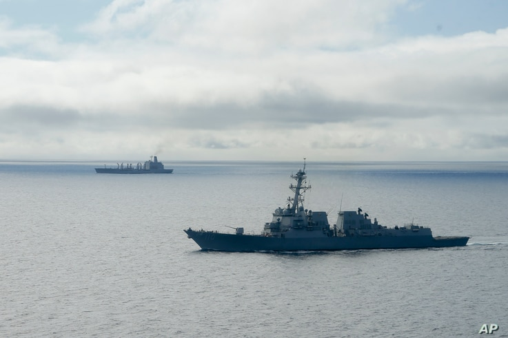FILE - The USS William P. Lawrence guided missile destroyer, below, awaits refueling from a tanker, above, off Coronado, Calif., Jan. 20, 2016.