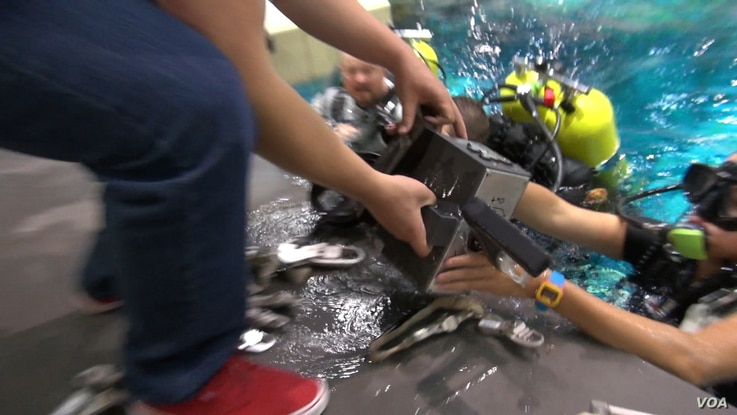 A diver hands a device to a West Virginia student. (G. Flakus/VOA)