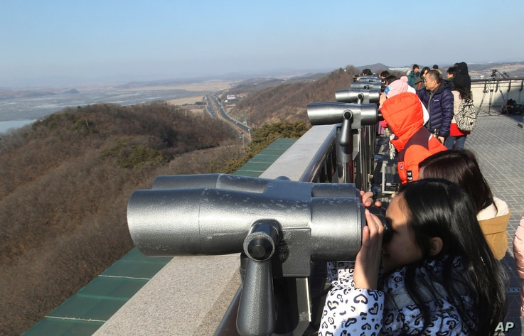 Visitors watch the North Korean side at the unification observation post near the border village of Panmunjom, which has separated the two Koreas since the Korean War, in Paju, South Korea, Feb. 7, 2016.