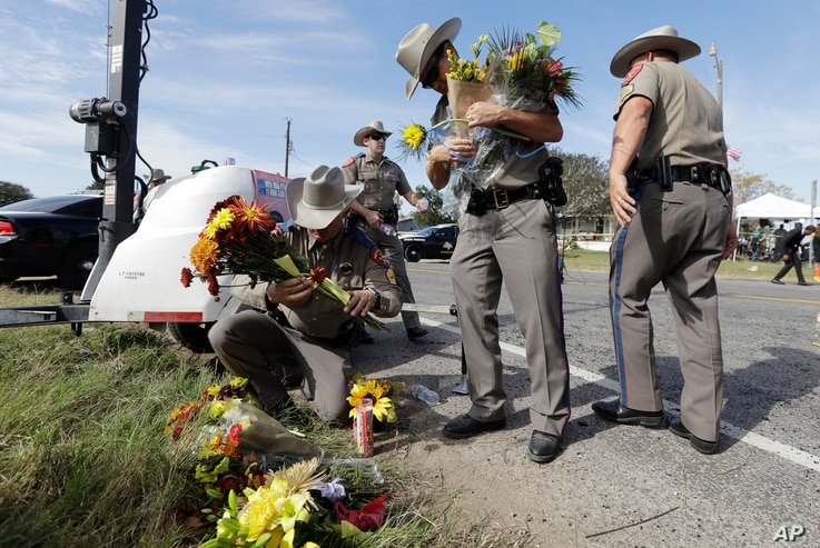 Law enforcement officials move flowers left at the scene of a shooting at the First Baptist Church of Sutherland Springs, Nov. 6, 2017, in Sutherland Springs, Texas.