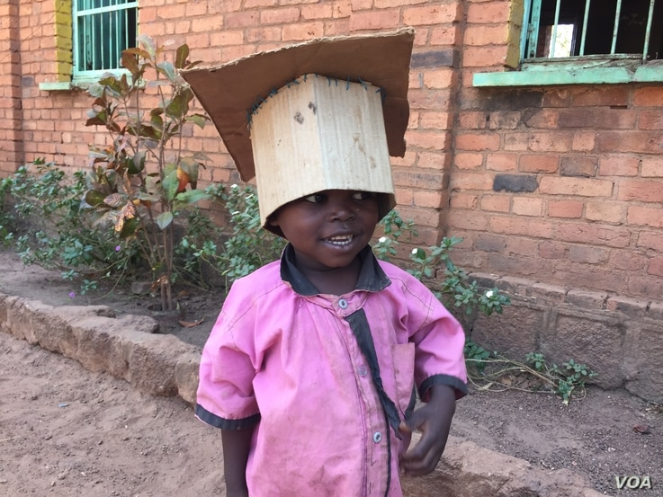 A young IDP shows off his homemade hat at the St. Mary Help of Christians Cathedral in Wau, Western Bahr el Ghazal, where his family is living. Dec. 8, 2016. (VOA/Jill Craig)
