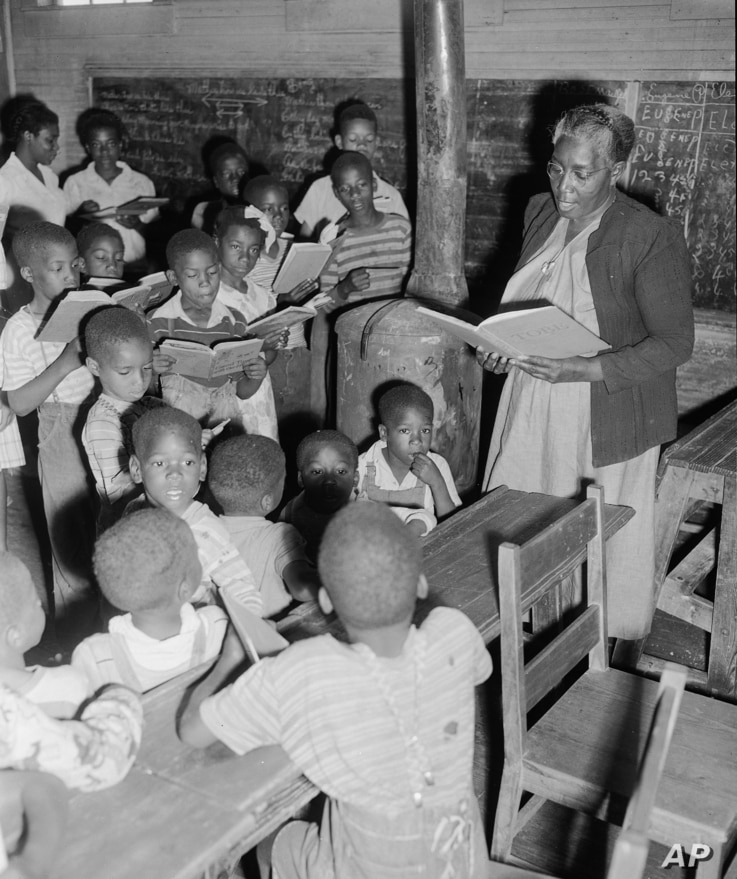"""""""Mama"""" Sarah L. Murphy teaches some of the 48 indigent and orphaned children in a two-room schoolhouse at Rockmart, Ga., June 23, 1950."""