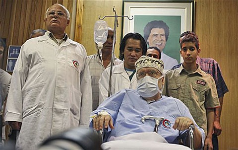 Libyan Abdel Baset al-Megrahi, who was found guilty of the 1988 Lockerbie bombing but released from his Scottish prison on compassionate grounds, is seen below a portrait of Libyan Leader Moammar Gadhafi, September 9, 2009 (file photo)