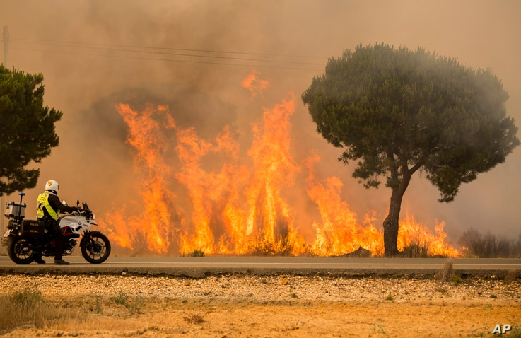 A military police officer stands by his motorcycle next to flames from a forest fire near Mazagon in southern Spain, June 25, 2017.