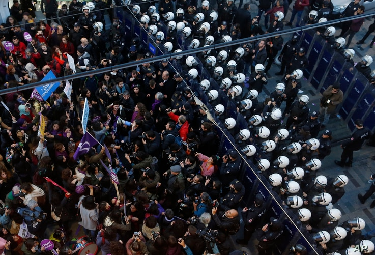 Turkish police officers in riot gear, right, block protesters during a rally against sexism and gender violence in central Istanbul, Turkey, Nov. 25, 2018.