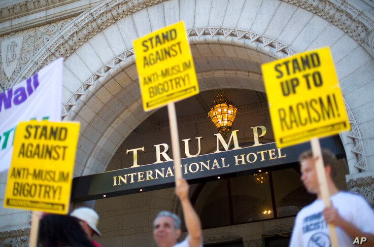 Demonstrators stand outside the Trump International Hotel during it's 'soft-opening' in downtown Washington, Sept. 12, 2016 in Washington.