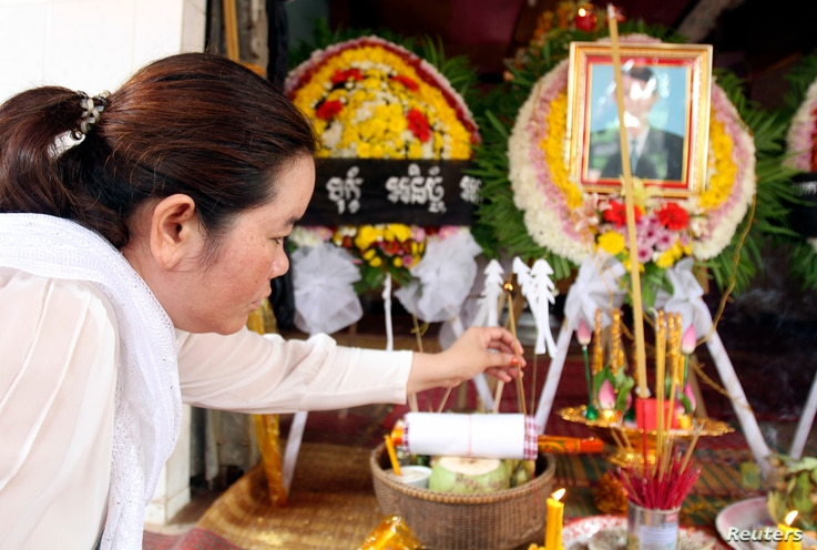 FILE - Sam Chanthy, 40, wife of Chut Wutty, director of the Phnom Penh-based environmental watchdog Natural Resource Protection Group, lights a stick of incense during Wutty's funeral at his house in Kandal province, April 28, 2012