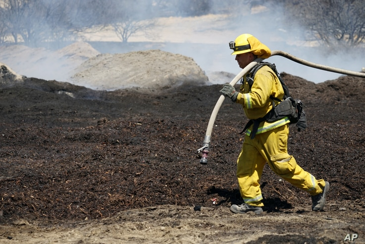 Firefighters water down scorched compost material at a property burned near Phelan, Calif., Aug. 19, 2016.