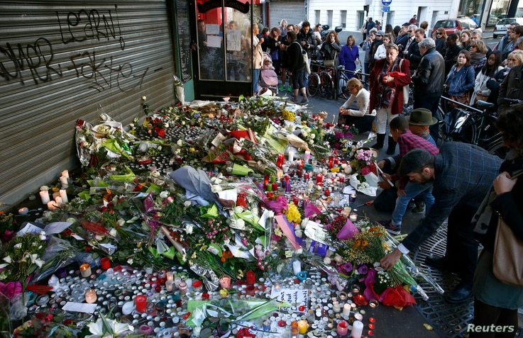 People pay their respect at one of the attack sites in Paris, Nov. 15, 2015.