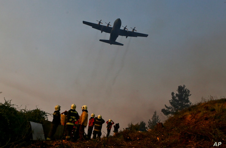 A Brazilian C-130 Hercules aircraft helps to fight the wildfire  approaching Chile's community of Dichato, Jan. 30, 2017.