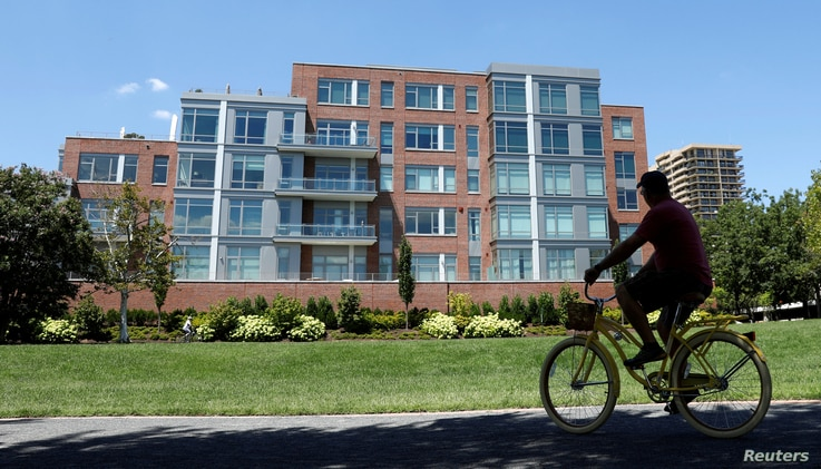A cyclist makes his way past a building in Alexandria, Virginia, Aug. 9, 2017, that contains a unit listed to Paul Manafort, President Donald Trump's former campaign manager, whose residence was raided by the FBI on July 26 as part of a special couns...