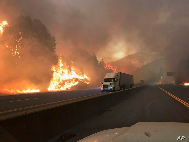 In this Sept. 5, 2018, photo released by the U.S. Forest Service, a truck drives next to the Delta Fire burning on Interstate 5 near Shasta-Trinity National Forest, Calif.