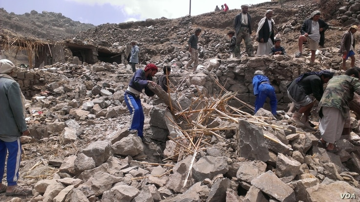 Locals help villagers that lost their homes recover their belongs that were scattered during the bombing of Hajar Aukaish, Yemen, April 2015. (A. Mojalli/VOA)