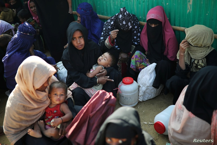 Rohingya refugee women wait outside of a medical center at Jamtoli camp in Cox's Bazar, Bangladesh, Jan. 22, 2018.