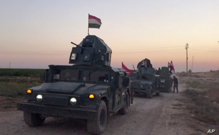 This image made from a video shows Iraqi soldiers on military vehicles in the Qatash area moving towards Kirkuk gas plant, Oct. 16, 2017.
