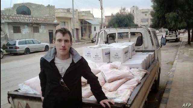 FILE - This undated photo shows Peter Kassig leaning against a truck at an unknown location.
