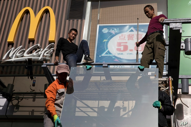 Workers install glass panels near a McDonald's in Beijing, Nov. 7, 2017. U.S. President Donald Trump is in Beijing amid mounting U.S. trade complaints, with limited prospects for progress on market access, technology policy and other sore points.