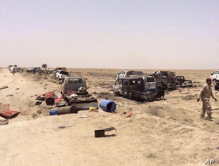 Iraqi security forces inspect vehicles belonging to escaping Islamic State militants outside Fallujah, Iraq, Wednesday, June 29, 2016.