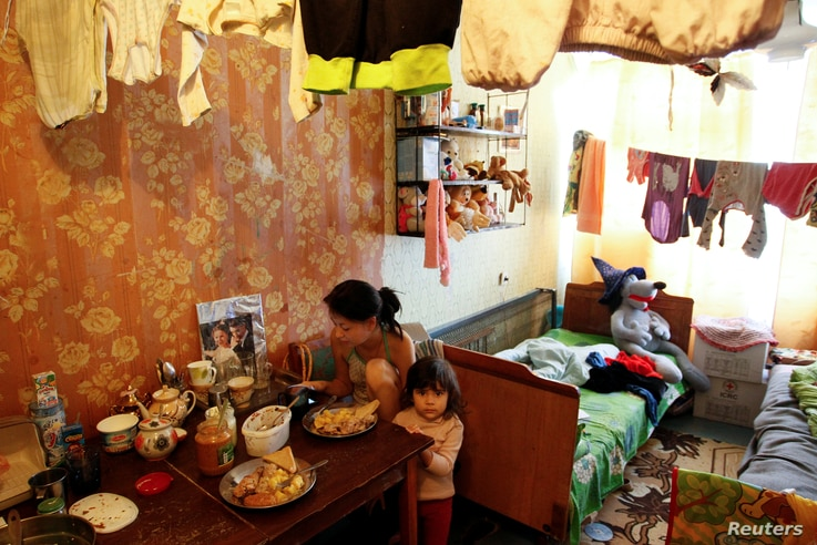 Residents who lost their home sit in a dorm room where they have lived for the past three years, in Donetsk, Ukraine, Sept. 28, 2017.