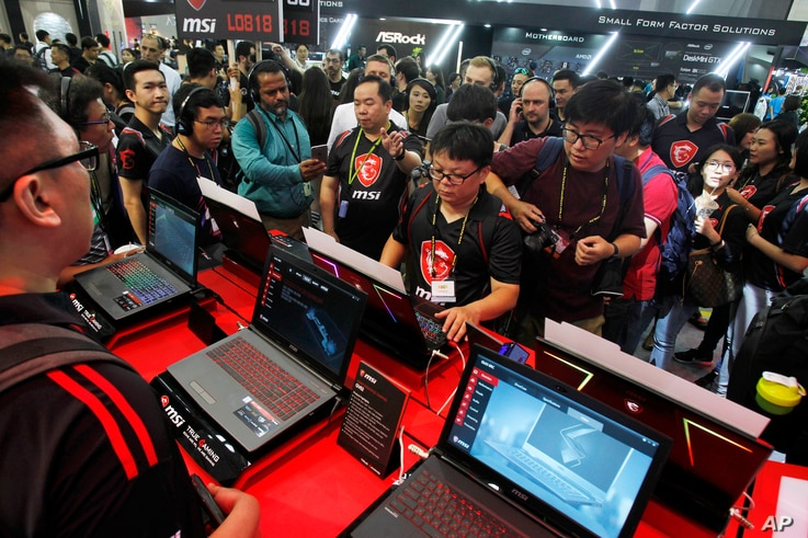 Visitors review new MSI computer products during the Computex Taipei, one of the world's largest IT expos, in Taipei, Taiwan, June 5, 2018.