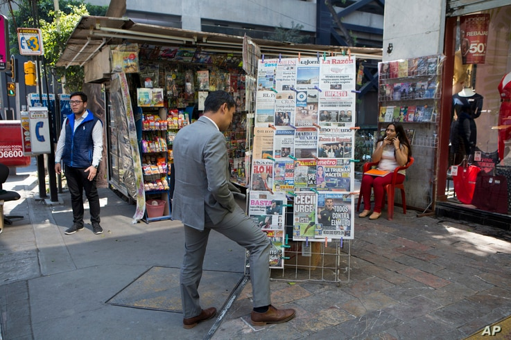 A man stops to read headlines, many featuring U.S. President Donald Trump's actions to jump-start construction on a promised border wall and his insistence that Mexico will foot the bill, in Mexico City, Jan. 26, 2017.