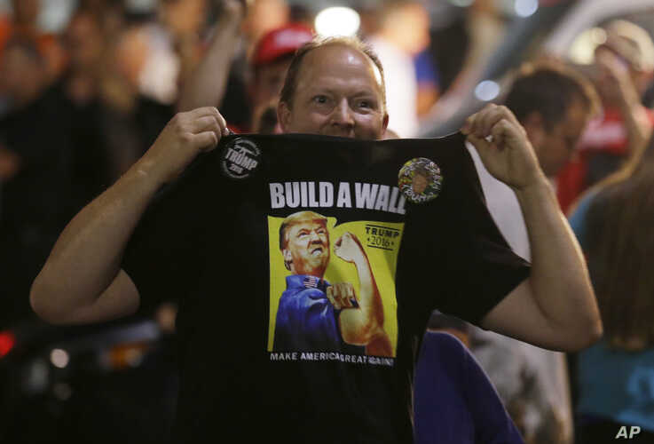 """A Donald Trump supporter holds up his shirt, which bears the slogan """"Build a Wall,"""" at a campaign rally for Trump, Aug. 30, 2016, in Everett, Wash."""