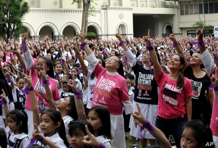 More than 3,000 students, teachers and nuns from the Catholic-run St. Scholastica's College in Manila, dance to take part in the global campaign to end violence against women and girls dubbed One Billion Rising, in Manila, Philippines, Feb. 13, 2015....