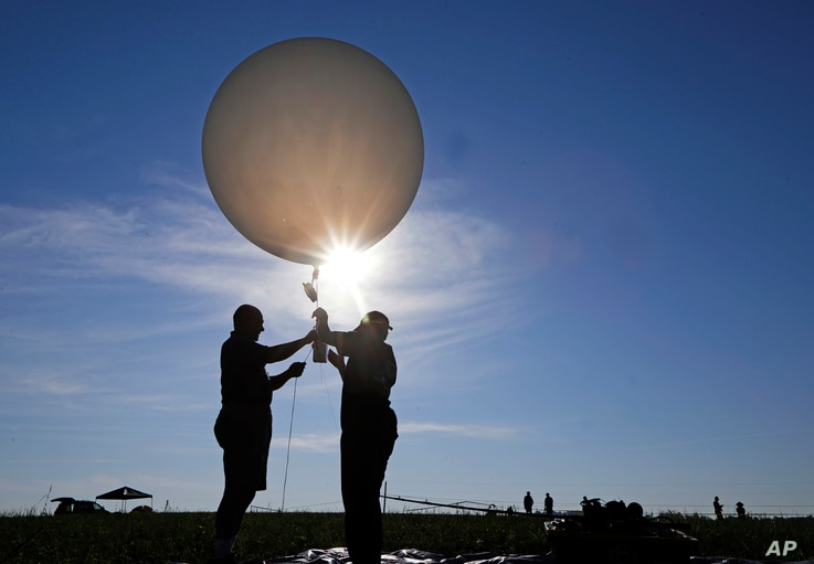 Mike Newchurch, left, professor of atmospheric chemistry at the University of Alabama in Huntsville, and graduate student Paula Tucker prepare a weather balloon before releasing it to perform research during the solar eclipse, Aug. 21, 2017, on the O...
