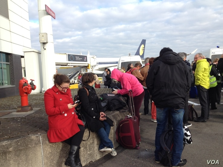 Passengers wait outside after being evacuated from Brussels airport, March 22, 2016. (N.deVries/VOA)