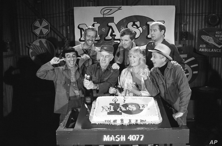 "FILE - Cast members of the ""M.A.S.H."" television series Jamie Farr, from front left, Harry Morgan, Loretta Swit, William Christopher and, from back left, Mike Farrell, Alan Alda and David Ogden Stiers celebrate during a party on the set of the popula..."