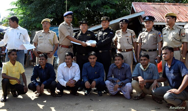 The seven Rohingya men to be deported sit as Indian and Myanmar security officials exchange documents before their deportation on India-Myanmar border at Moreh in the northeastern state of Manipur, India, Oct. 4, 2018.