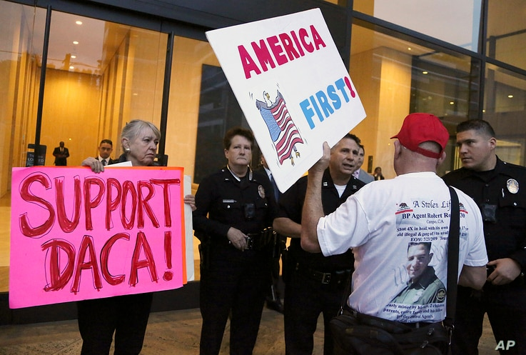 FILE - A supporter of President Donald Trump challenges police officers and a Deferred Action for Childhood Arrivals (DACA) program advocate during a rally outside the office of California Democratic Sen. Dianne Feinstein in Los Angeles, California,