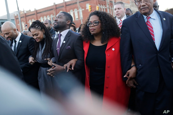 "Oprah Winfrey locks arms with David Oyelowo, left, who portrays Martin Luther King Jr. in the movie ""Selma,"" Ava DuVernay, the director of ""Selma"" and rapper Common, far left, as they march to the Edmund Pettus Bridge in honor of Martin Luther King J..."