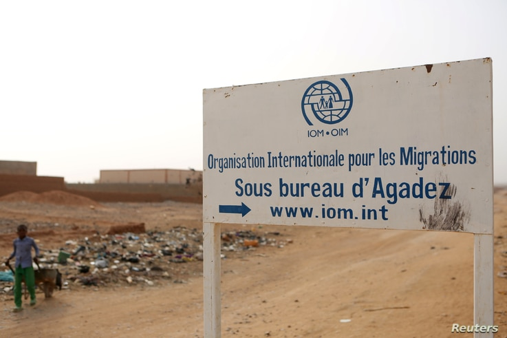 FILE - A boy walks past a signboard for the International Migration Organization's transit center in Agadez, Niger, May 11, 2016.