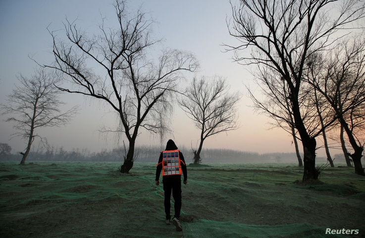 Artist Liu Bolin wearing a vest with 24 mobile phones walks in smog as he live broadcasts air pollution in the city on the fourth day after a red alert was issued for heavy air pollution in Beijing, China, Dec. 19, 2016.