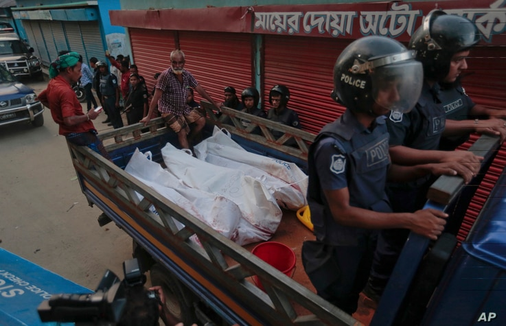 Bangladesh policemen drive off in a mini truck with bodies of suspected militants after a raid in Narayanganj district near Dhaka, Bangladesh, Aug.27, 2016.