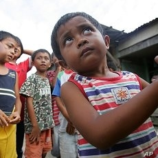 Arfaisal Marsaleh, 2, a stateless child, holds on to his mother as he plays with his friends in a slum village in Kinarut, in Malaysia's Sabah state on the Borneo island. (file photo)