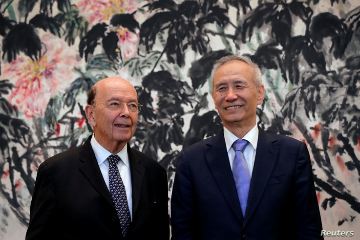 U.S. Commerce Secretary Wilbur Ross, left, chats with Chinese Vice Premier Liu He during a photograph session after their meeting at the Diaoyutai State Guesthouse in Beijing, China, June 3, 2018.