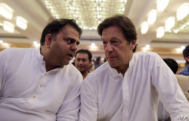 Pakistani cricketer-turned-politician and head of the Pakistan Tehreek-i-Insaf  Imran Khan,r ight,  speaks with his party spokesperson Fawad Chaudhry before presenting their party manifesto for the forthcoming general election in Islamabad on July 9,...
