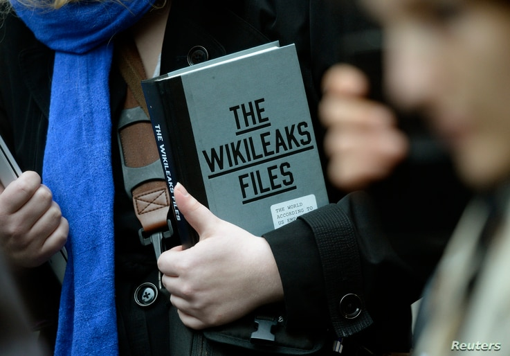 A supporter of WikiLeaks founder julian Assange holds a copy of The WikiLeaks Files outside the Ecuadorian embassy in central London, Britain Feb. 5, 2016.