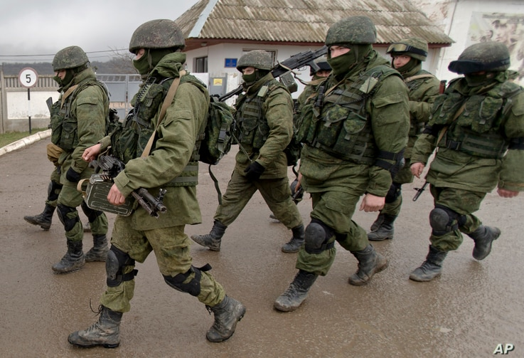 FILE - Pro-Russian soldiers march outside an Ukrainian military base in Perevalne, Crimea, March 20, 2014.