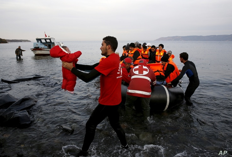 A Red Cross volunteer carries a Syrian refugee baby off an overcrowded raft at a beach on the Greek island of Lesbos Nov. 16, 2015.