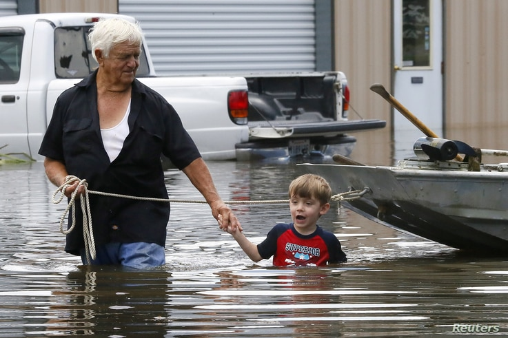 Richard Rossi and his 4 year old great grandson Justice wade through water in search of higher ground after their home took in water in St. Amant, Louisiana.
