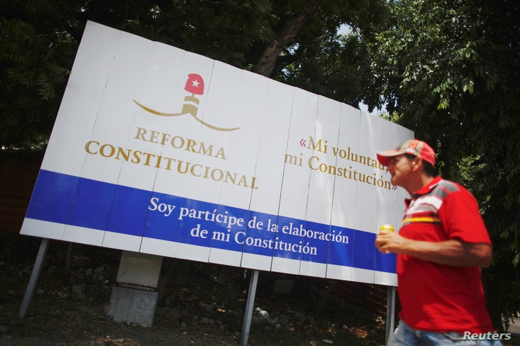 A Cuban walks past a billboard promoting the public political discussion to revamp a Cold War-era constitution in Havana, Aug. 10, 2018.